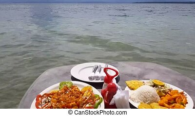 Caribbean food served in table on the beach.