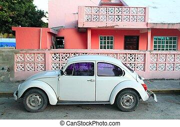 Caribbean pink house tropical retro car facade in Mexico