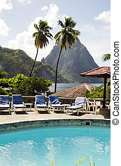 Caribbean Sea resort swimming pool view twin piton peaks mountains with coconut palm trees Soufriere St. Lucia