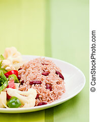 Caribbean style rice cooked with red kidney beans served with fresh garden vegetables. Shallow DOF.