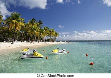 Beautiful caribbean lagoon with three jetskis