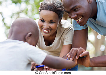 african couple helping their little son to ride bicycle