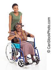 african daughter pushing senior mother on wheelchair -...