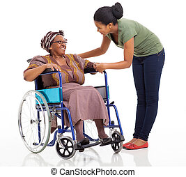 caring african girl talking to disabled senior mother on white background