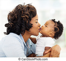 caring african mother kissing her daughter