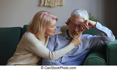 Caring aged wife comforting talking to upset elderly husband