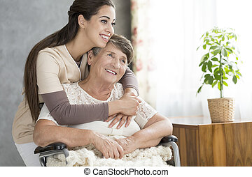 Caring and smiling woman hugging happy grandmother