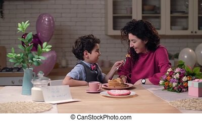 Caring arab son feeding mom with pancakes - Festively...