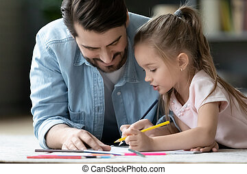Caring dad drawing in album with little daughter