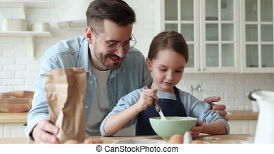 Caring dad teaching child daughter learning making dough in kitchen