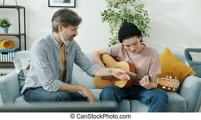 Caring dad mature man is teaching son teenager how to play guitar talking and gesturing indoors at home. Music and creative family activities concept.