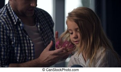 Caring daddy making a hairstyle for his pretty daughter