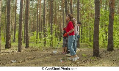 Eco-friendly diverse multiracial young friends in protective gloves with work tools picking up plastic litter in trash bags during spring cleaning in forest, caring for nature. Environment pollution.