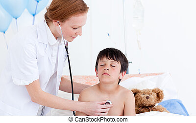Caring doctor examining a little boy