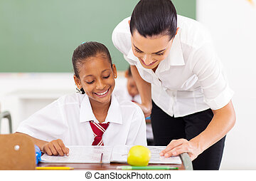 caring elementary school teacher helping student in classroom