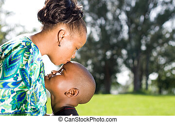 caring family - a caring african mother kissing her sons...