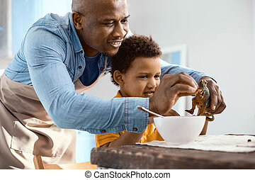 Caring father feeding cereals to his sons toy dinosaur