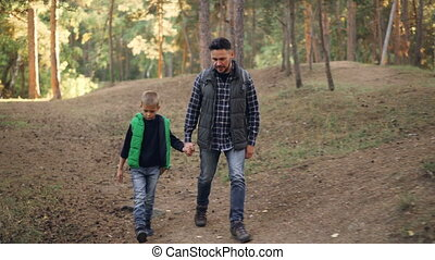 Caring father is hiking with his child in forest on sunny autumn day, man and boy are walking and talking holding hands. Parenthood and childhood concept.