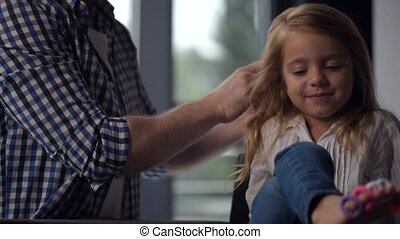 Caring father making a hairstyle for his smiling daughter -...