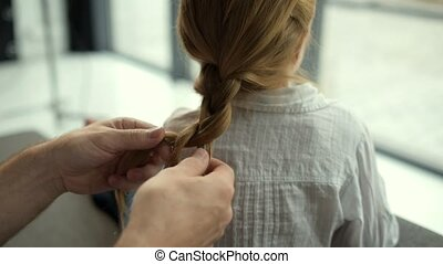Caring father plaiting hair of his daughter at home