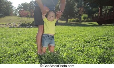 Caring father teaching infant boy to walk on grass