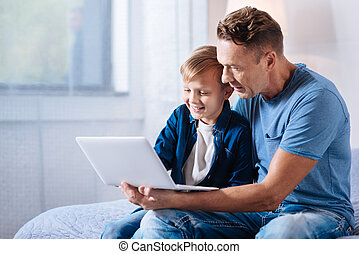 Caring father watching cartoons with his son on laptop