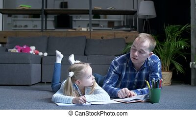 Caring father with preschool girl studying at home