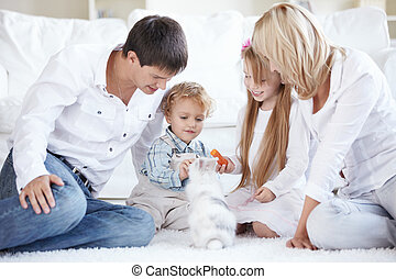 Caring for a pet - A happy family with children feeding a...