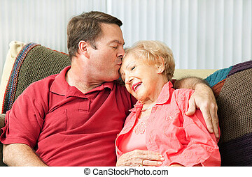 Caring For Elderly Mother - Senior woman gets a kiss from...