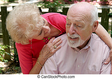Caring For Husband - A senior couple. The wife is caring for...