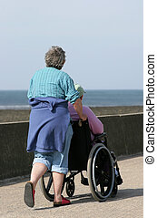 Caring for the Disabled - Elderly woman pushing a man in a...