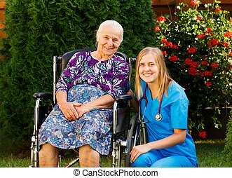 Kind doctor taking care of elderly woman at the nursing home.