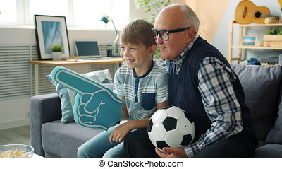 Caring grandad and happy boy are watching football on TV holding foam hand and ball cheering feeling excited. Happiness, family and childhood concept.