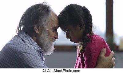 Caring grandfather consoling his little sad girl