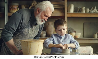 Caring grandfather is watching his grandchild molding clay on throwing wheel, making low ceramic vase then washing hands in large bowl. Pottery and family concept.