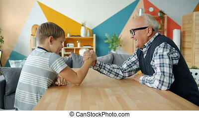 Caring grandfather is teaching boy to wrestle having fun doing sports at home, laughing grandad is winning talking to kid. Family, leisure time and lifestyle concept.