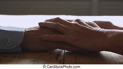 Caring grandma wife holding hands of elderly husband, closeup view