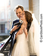 caring groom hugging beautiful bride on street at cold day