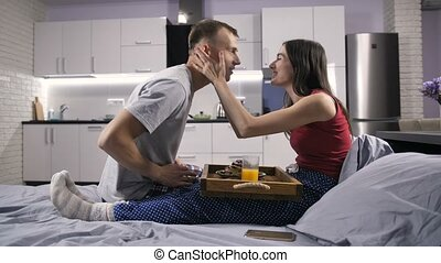 Caring husband serving breakfast in bed for wife