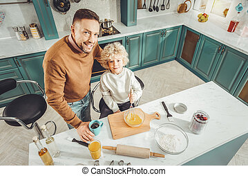 Caring loving father and son making breakfast for their family