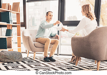 Caring loving wife giving napkin to her husband