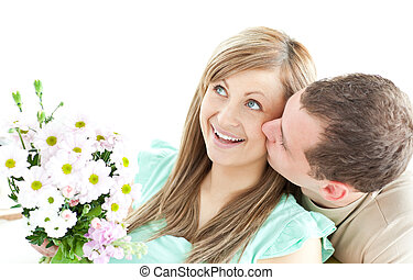 Caring man giving a bouquet to his girlfriend against a ...