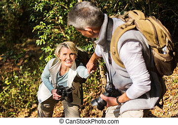 man helping his wife climbing mountain