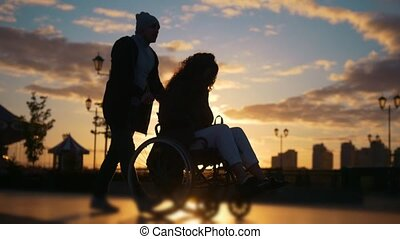 Caring man with a disabled woman in wheelchair walking...
