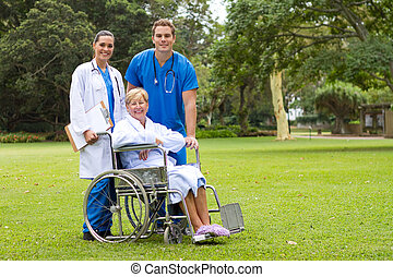 caring medical staff with patient in the park