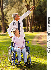 mid age doctor taking disabled senior patient for a walk