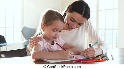 Caring mom embrace help kid daughter drawing picture with ...