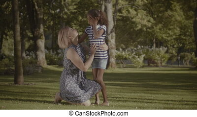 Caring mother adjusting daughter's clothes outdoors