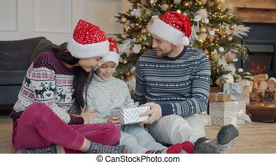 Caring mother and father congratulating kid on Christmas ...