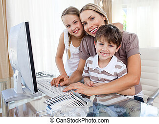 Caring mother and her children at a computer
